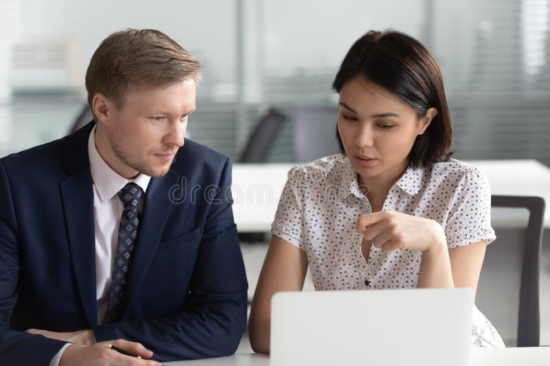 Asian businesswoman and Caucasian businessman working discussing project stock photography