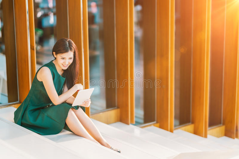 Asian businesswoman or college student using digital tablet at sunset. Modern office or library scene, business communication, gadget technology or education stock photos