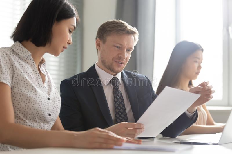 Asian businesswoman discussing legal documents with Caucasian businessman royalty free stock photography