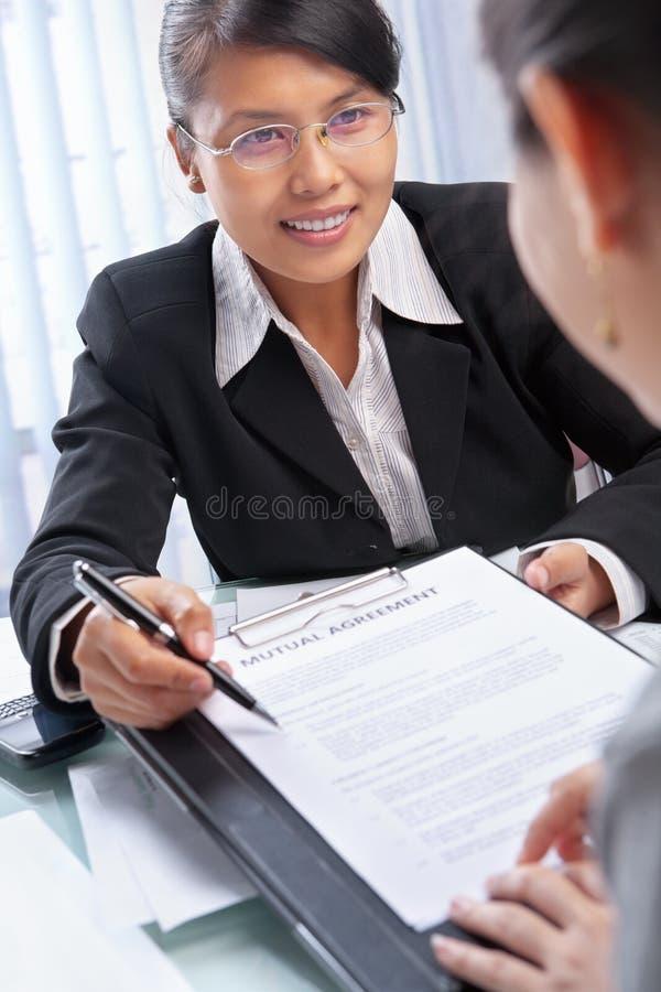 Asian businesswoman explaining document to client