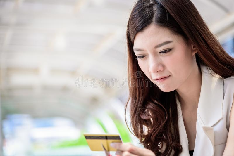 The asian businesswoman has destroying a credit card with red sc. Issors stock photo