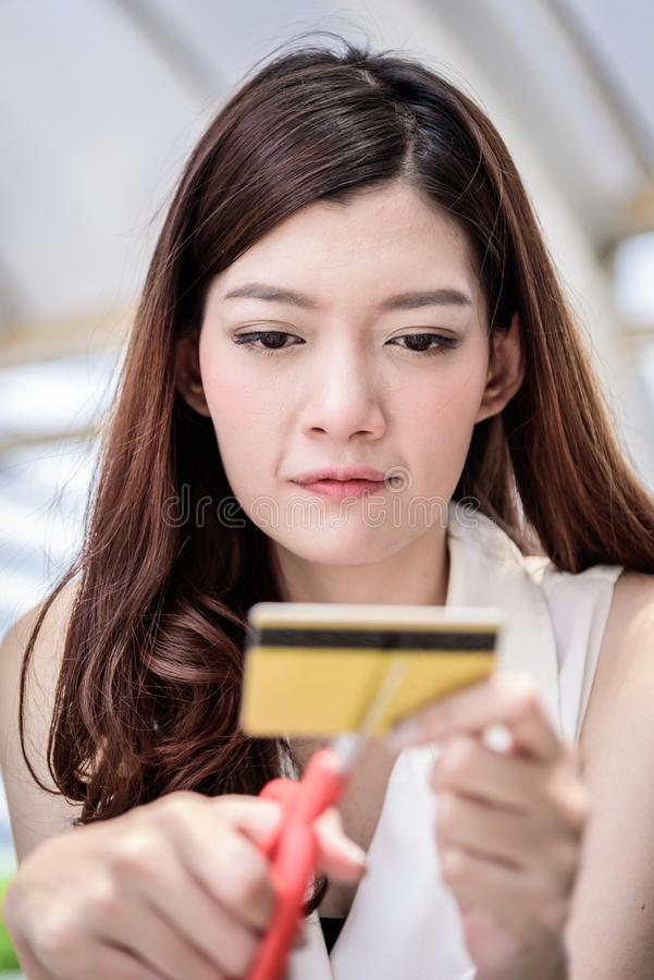 The asian businesswoman has destroying a credit card with red sc. Issors stock image