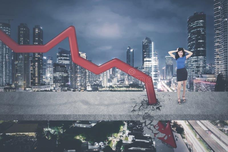 Asian businesswoman standing near downward arrow royalty free stock photo