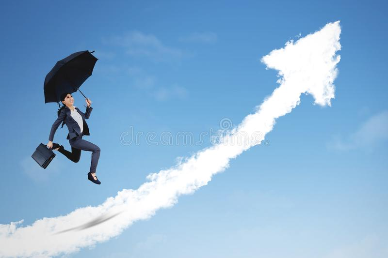 Asian businesswoman jumping with upward arrow. Asian businesswoman holding a suitcase and umbrella while jumping with clouds shaped upward arrow in the sky royalty free stock images