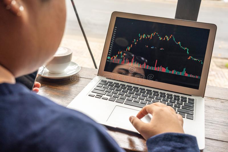 Asian businesswoman looking at stock market trading graph on computer. Young businesswoman looking at stock market trading graph on computer stock images