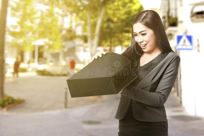 Asian businesswoman opening the black shopping bags in the city royalty free stock photos