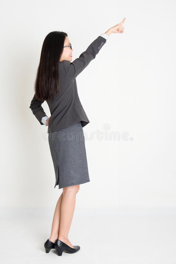 Asian businesswoman pointing away royalty free stock photo