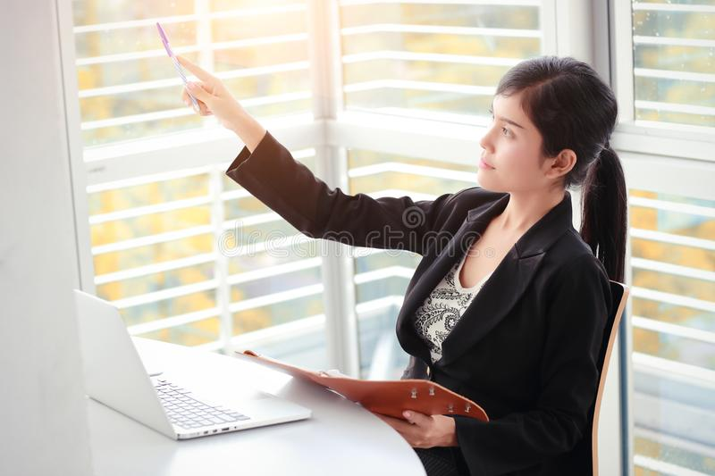 Businesswoman pointing at something with notebook while using laptop computer stock images