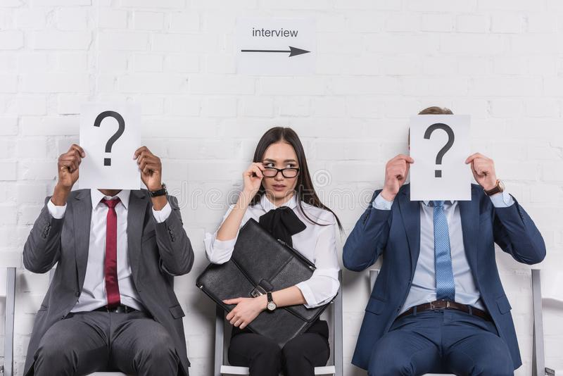 asian businesswoman sitting near multicultural businessmen that holding cards with question marks while waiting royalty free stock photos
