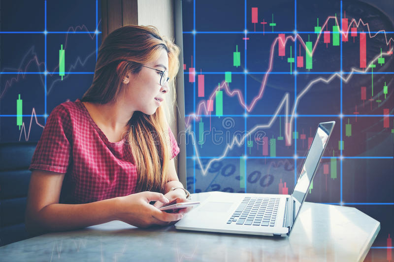asian businesswoman sitting amd working Laptop Stock market exchange information and Trading graph stock images