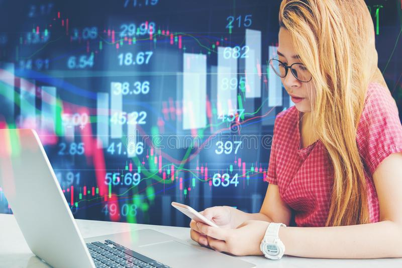 Asian businesswoman sitting on working space and looking the Stock market exchange information and Trading graph.  royalty free stock images
