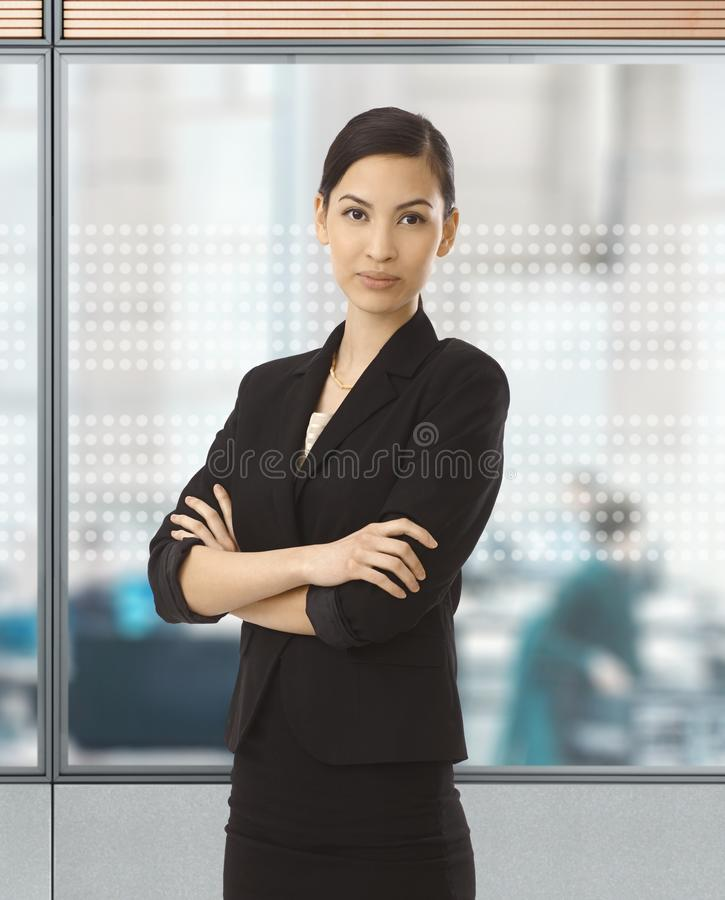 Asian businesswoman standing at glass wall royalty free stock images