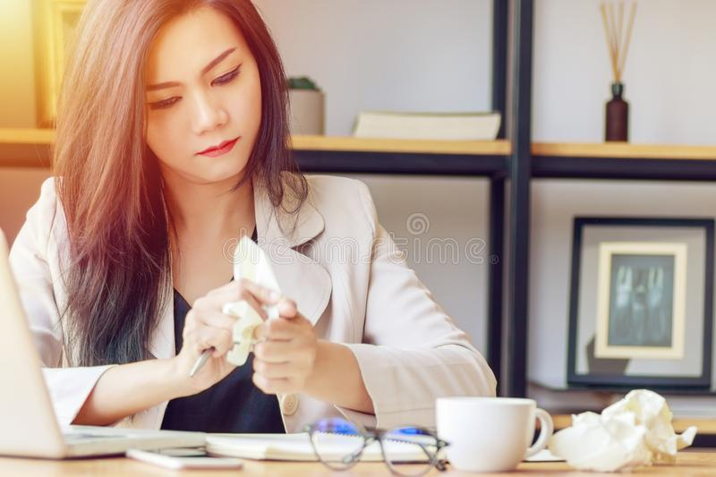 Asian businesswoman stressed with unsuccessful work, squeeze paper in hand sitting at office desk covered with crumpled paper stock photos
