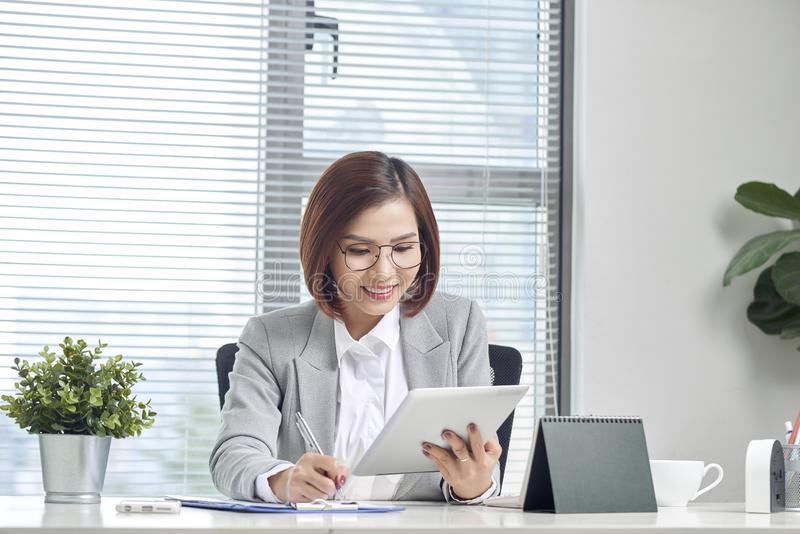 Asian businesswoman working with tablet computer at office desk stock image