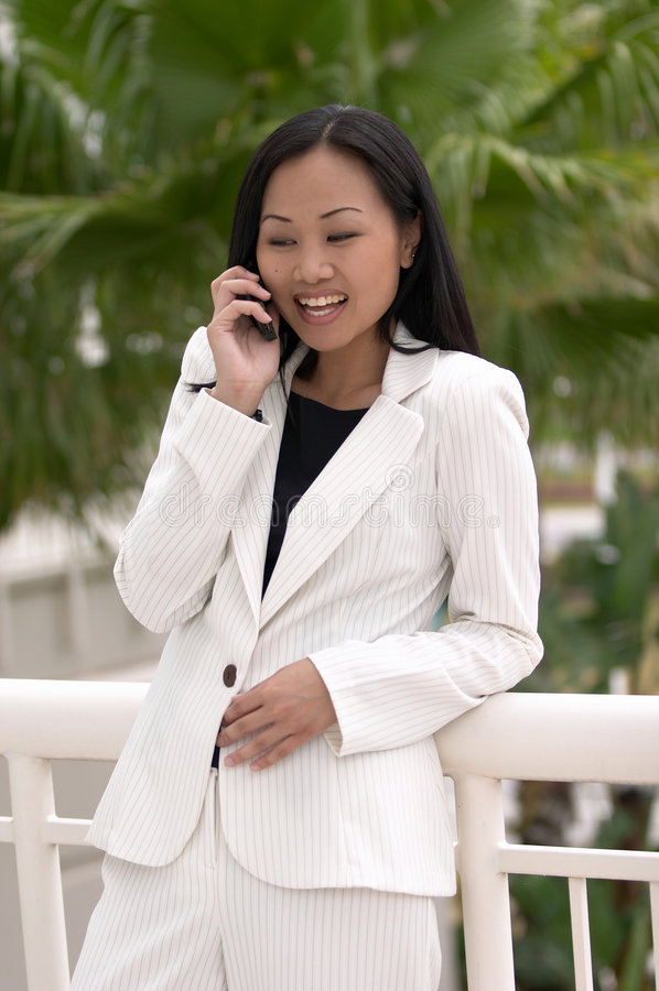 Asian Busness Woman Laughing with Cell Phone royalty free stock image