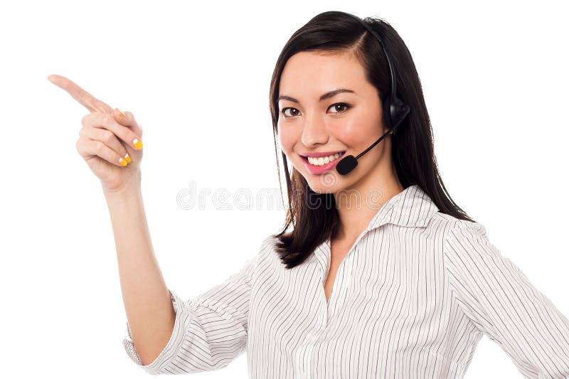 Asian call center executive pointing away stock image