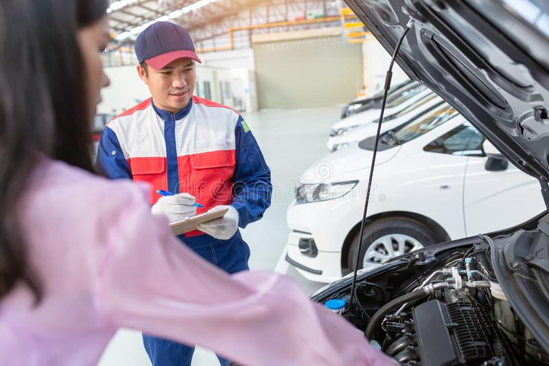 Asian car mechanic and customer Woman talking to a car mechanic in Car service center, both are standing next to the car royalty free stock images