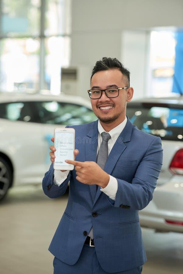 Asian car salesman in auto salon royalty free stock image