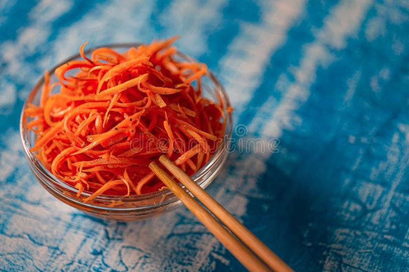 Asian carrot salad with spices and garlic on the plates. Korean carrot pickled salad on blue background. Fresh carrot on the plates, preserved in vinegar stock image