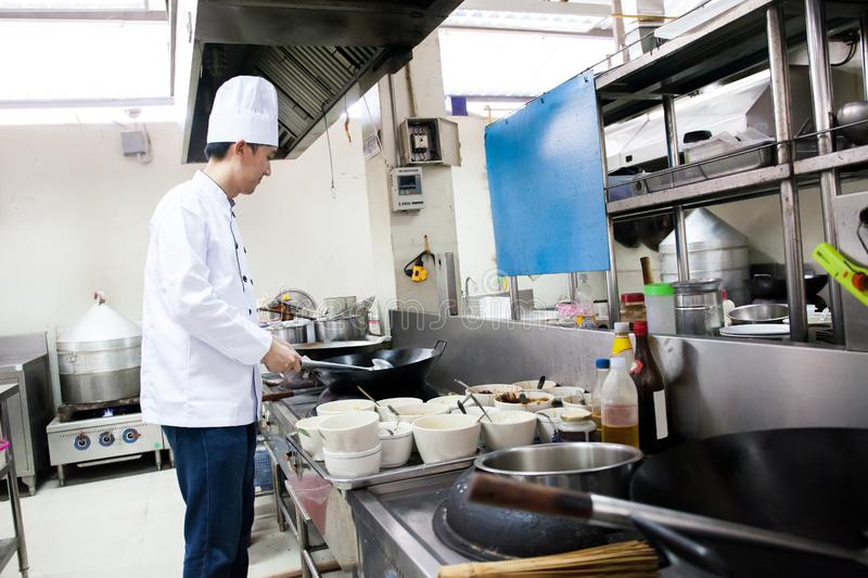 Chef in hotel or restaurant kitchen busy cooking stock photo