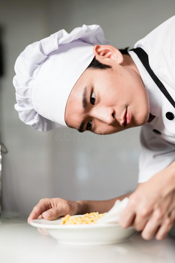 Asian chef plating up a bowl of food royalty free stock photography