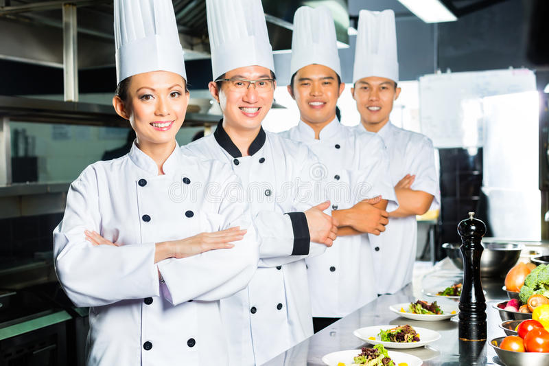 Asian Chef in restaurant kitchen cooking. Asian Indonesian and Chinese chefs along with other cooks in restaurant or hotel commercial kitchen cooking, finishing royalty free stock images