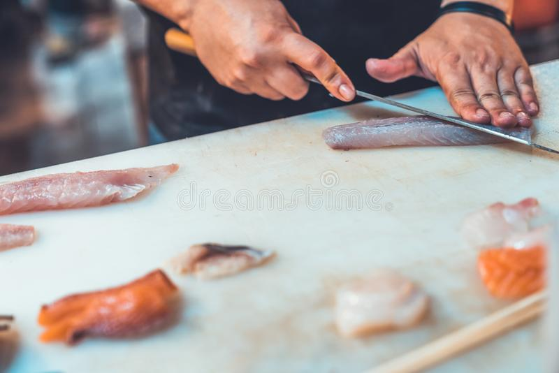 Asian Chef slicing raw fish on chopping board, cooking sushi menu. Japanese famous traditional food, seafood, street food concept. Asian Chef slicing raw fish on royalty free stock image