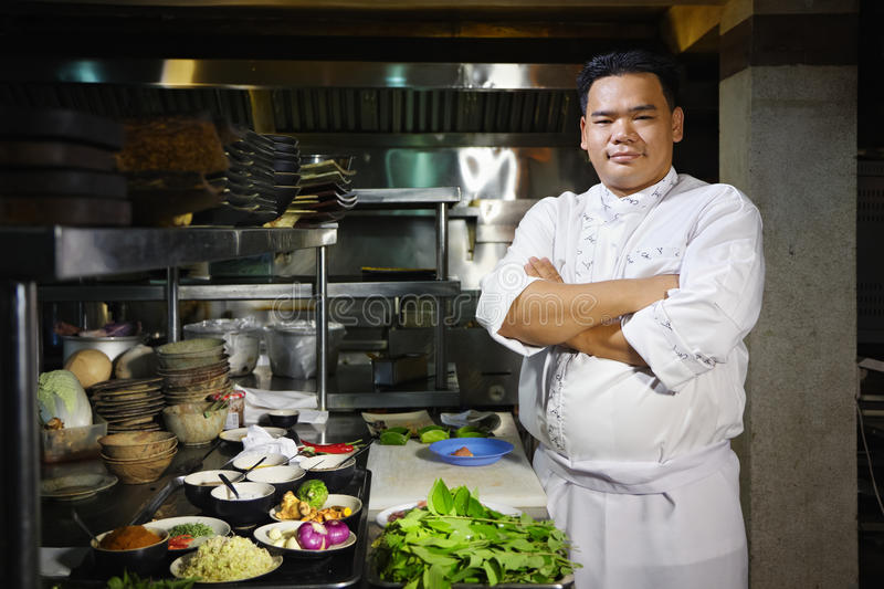 Asian chef smiling at camera in restaurant kitchen. Portrait of adult man at work as chef in the kitchen of an Asian restaurant, posing with arms crossed royalty free stock photography
