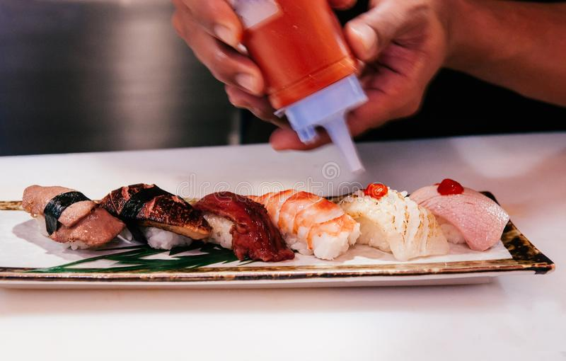 Chef squeezed hot sauce onto many kind of Japanese Sushi on cera. Asian Chef squeezed hot sauce onto many kind of Japanese Sushi on ceramic plate, Otoro, shrimp stock photo