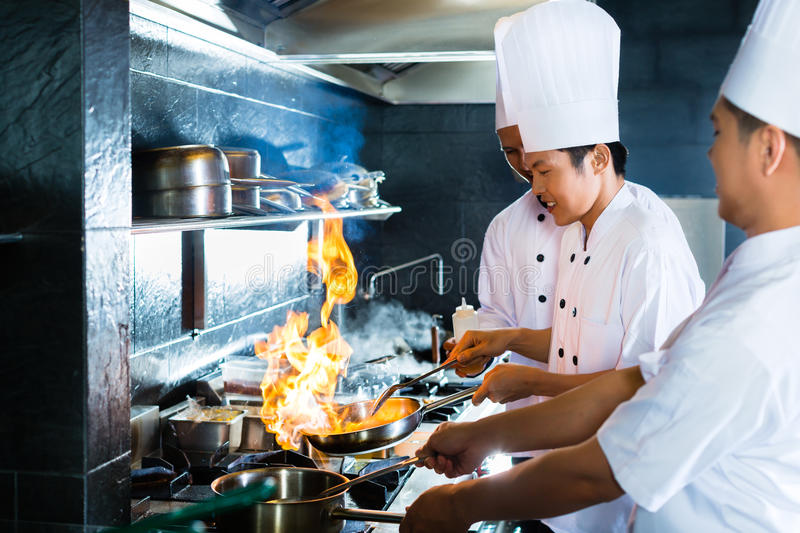 Asian chefs cooking in Restaurant. Side view of chefs cooking together stock image