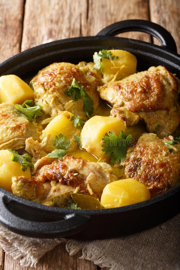 Asian chicken coconut curry with potatoes close-up in a pan. vertical. Asian chicken coconut curry with potatoes close-up in a pan on the table. vertical royalty free stock image