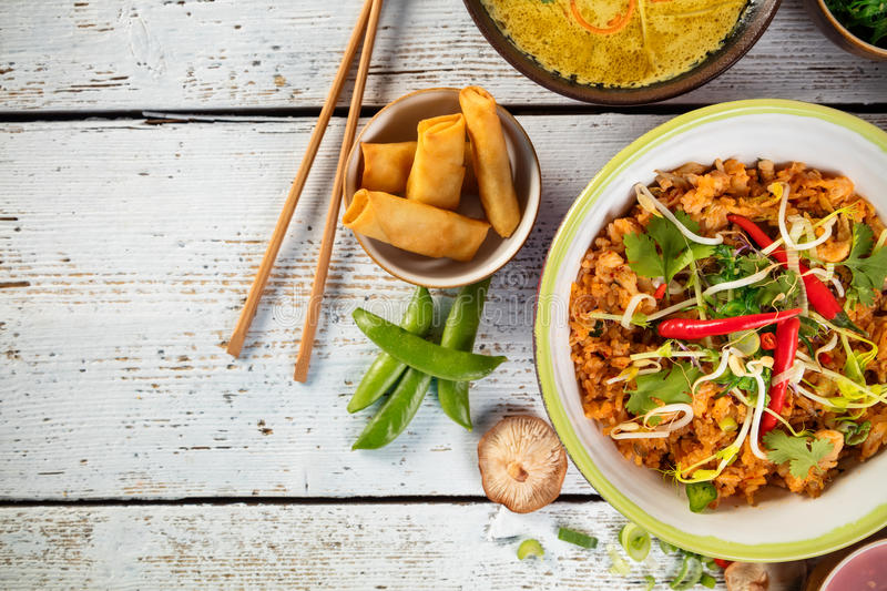 Asian chicken curry and prawns with rice and sushi pieces. Asian chicken and prawns curry with rice and spring rolls pieces, top view, served on old wooden stock images