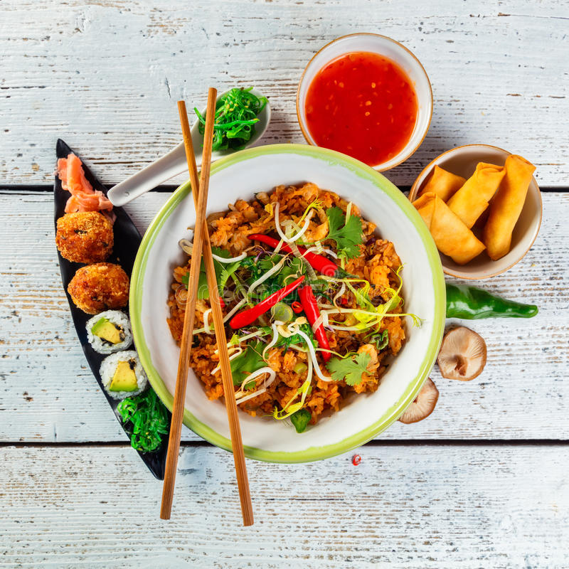 Asian chicken curry and prawns with rice and sushi pieces. Asian chicken and prawns curry with rice and sushi pieces, top view, served on old wooden planks stock photo