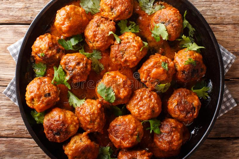 Asian chicken meatballs in a creamy coconut sauce with red curry closeup on a plate. horizontal top view. Asian chicken meatballs in a creamy coconut sauce with stock photo