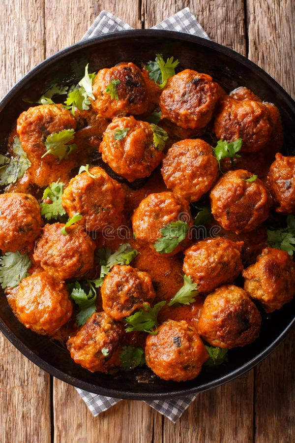Asian chicken meatballs in a creamy coconut sauce with red curry closeup on a plate. Vertical top view. Asian chicken meatballs in a creamy coconut sauce with stock photo