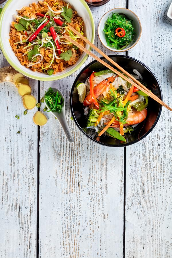 Asian chicken and prawns curry with rice and fresh vegetable. Top view, served on old wooden planks stock image