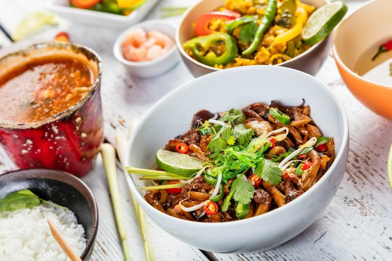 Asian chicken and prawns curry with rice and spring rolls pieces. Served on old wooden planks royalty free stock photography