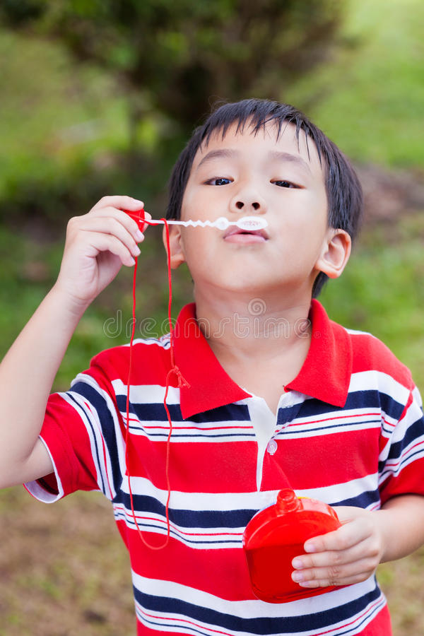 Asian child blowing soap bubbles in summer park, nature backgrou stock images