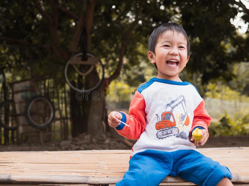 Asian child boy laughing with happy funny face while playing bubbles outdoor with natural rural background. stock images