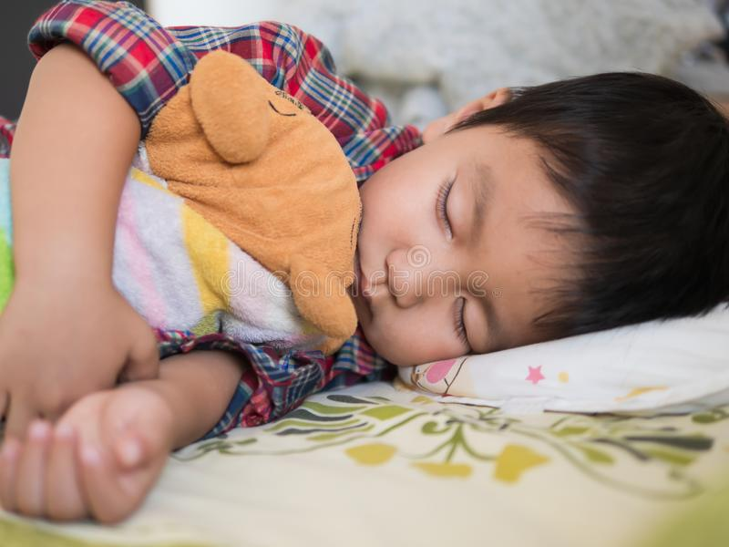 Asian child boy sleeping on bed in bed room. Young kid hugging favorite teddy bear. royalty free stock photography