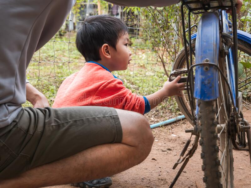 Asian child boy turning bicycle pedal to see wheel spinning. Young kid in orange shirt playing, learning outdoor with father in rural countryside natural royalty free stock photography