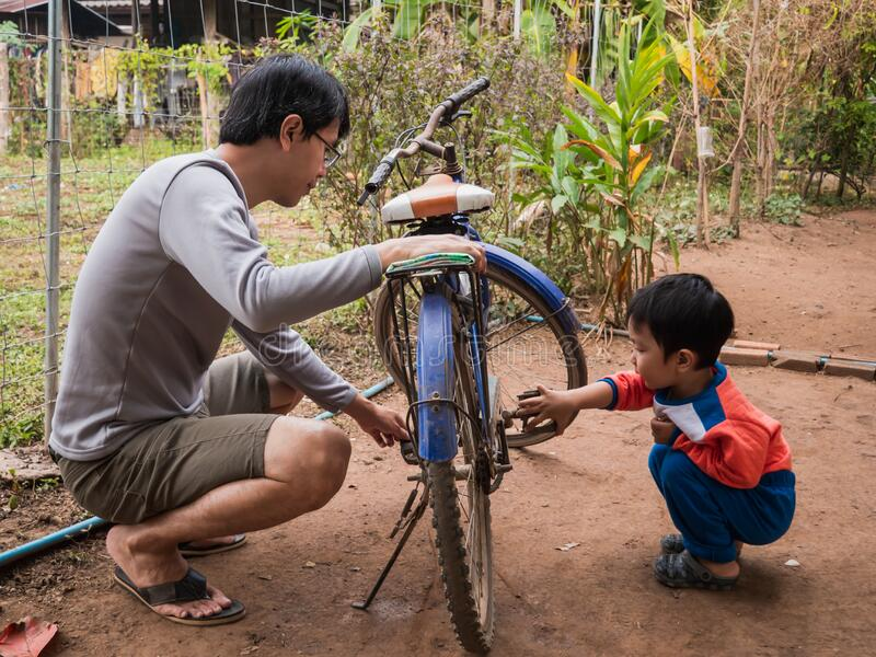 Asian child boy turning bicycle pedal to see wheel spinning. Young kid in orange shirt playing, learning outdoor with father in rural countryside natural stock photography