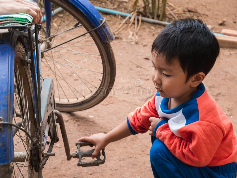 Asian child boy turning bicycle pedal to see wheel spinning. Young kid in orange shirt playing. royalty free stock photos