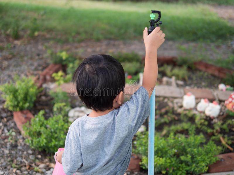 Asian child boy turning sprinkler in garden at home. Young kid do gardening in summer holiday. royalty free stock photos