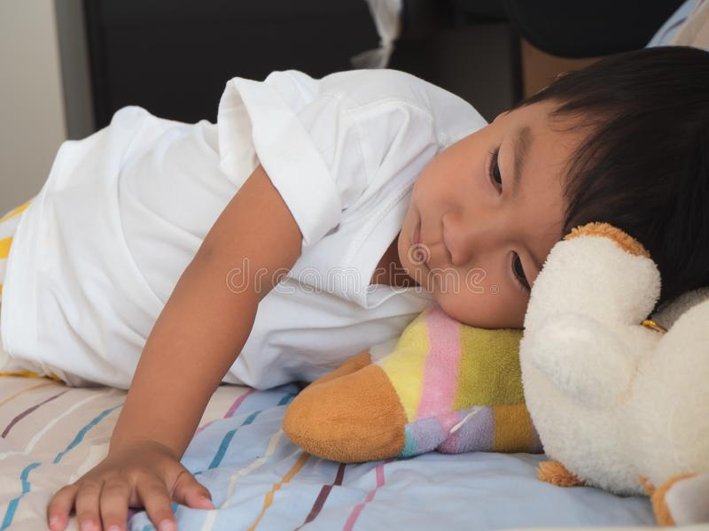 Asian child boy in white t-shirt lying on bed in bedroom at home with happy relax face. royalty free stock image