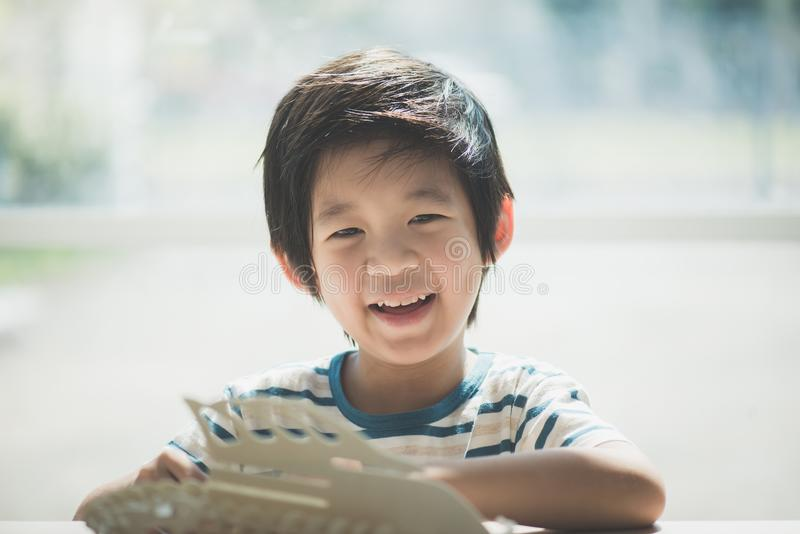 Asian child builds a toy of wood stock photo