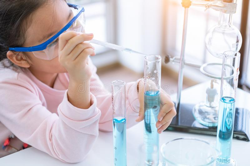 Asian child chemist holding flask and test tube in hands in lab learning chemistry experiment. Scientist chemistry and science stock image
