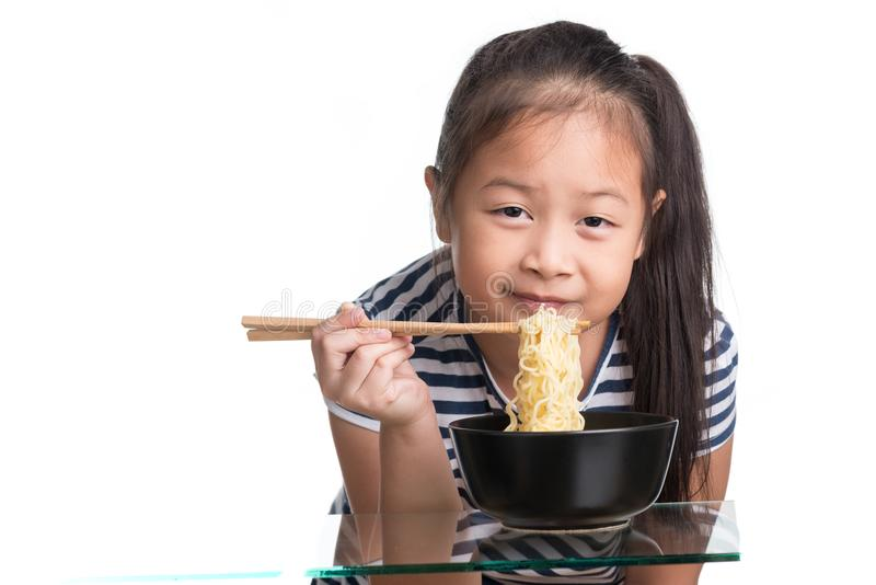 Asian child girl age 7 year , eating Instant noodles on white b royalty free stock image