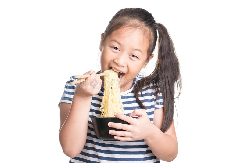 Asian child girl age 7 year , eating Instant noodles on white b stock images