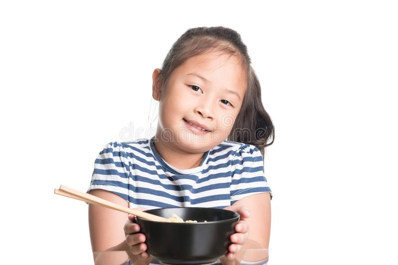 Asian child girl age 7 year , eating Instant noodles on white b stock photography